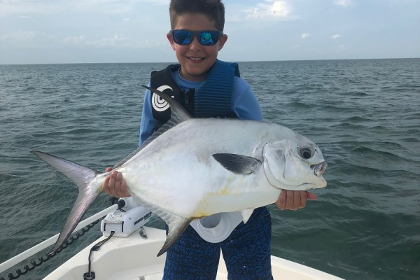 Young boy catches permit on family friendly fishing charter at Hawks Cay Resort in the Florida Keys