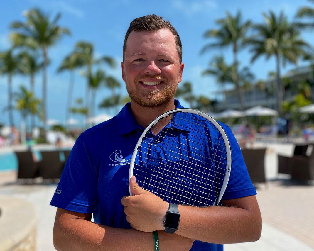 headshot of tennis director peyton smith holding a tennis racquet